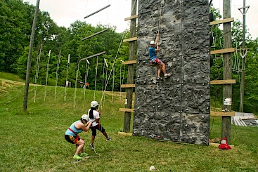 Staff demonstrating climbing wall saftey