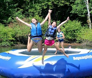 Jumping off trampoline into Leesville Lake at our overnight summer camp.